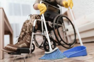Man in wheelchair using extended brush and broom