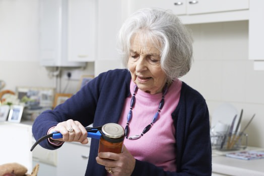 Woman using a jar opener aid