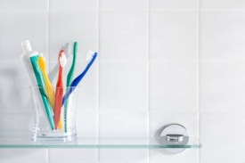 Toothbrushes in a glass in the shower
