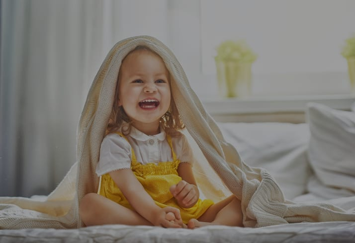 young toddler with blanket on head