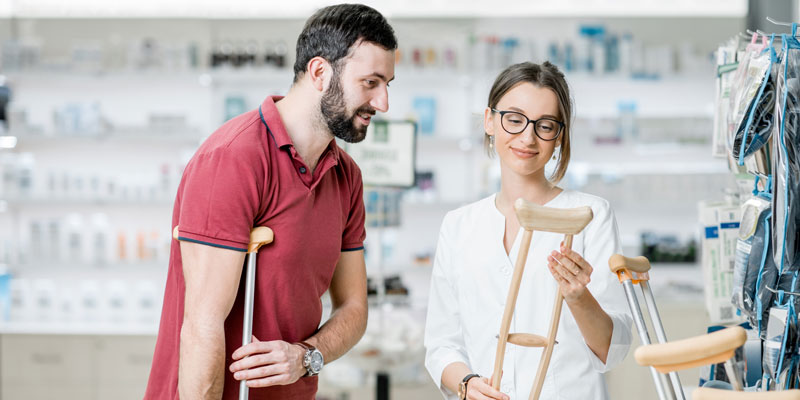 Woman helping man select crutches