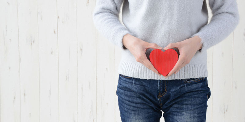 Woman holding a red heart in-front of bowels